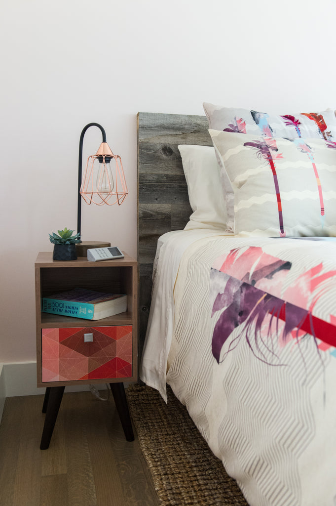 A diy reclaimed headboard has pillows piled against it in a feminine bedroom