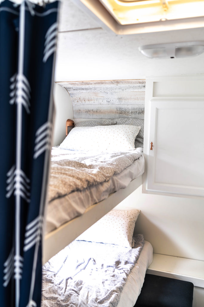 DIY wood plank wall in a sleeping area of a travel trailer.