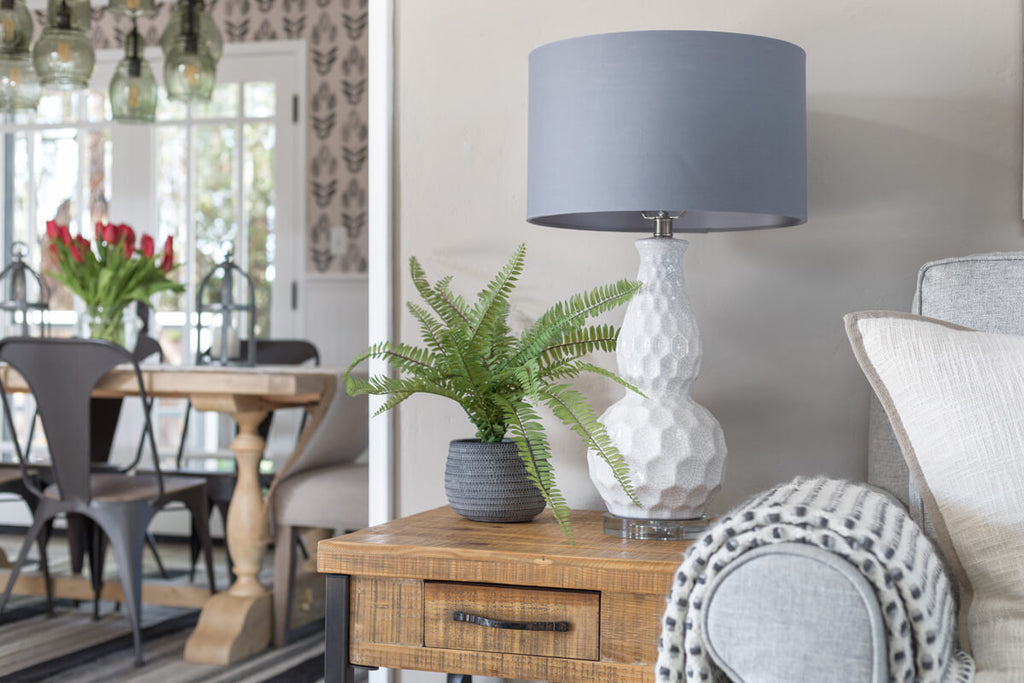 A modern farmhouse living room side table with white lamp and green fern on top