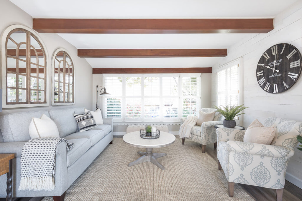 a modern farmhouse living room with sofa and arm chairs