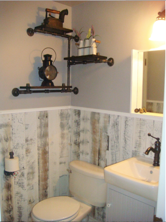 Light colored peel and stick wainscoting installed vertically wraps around small half bathroom.