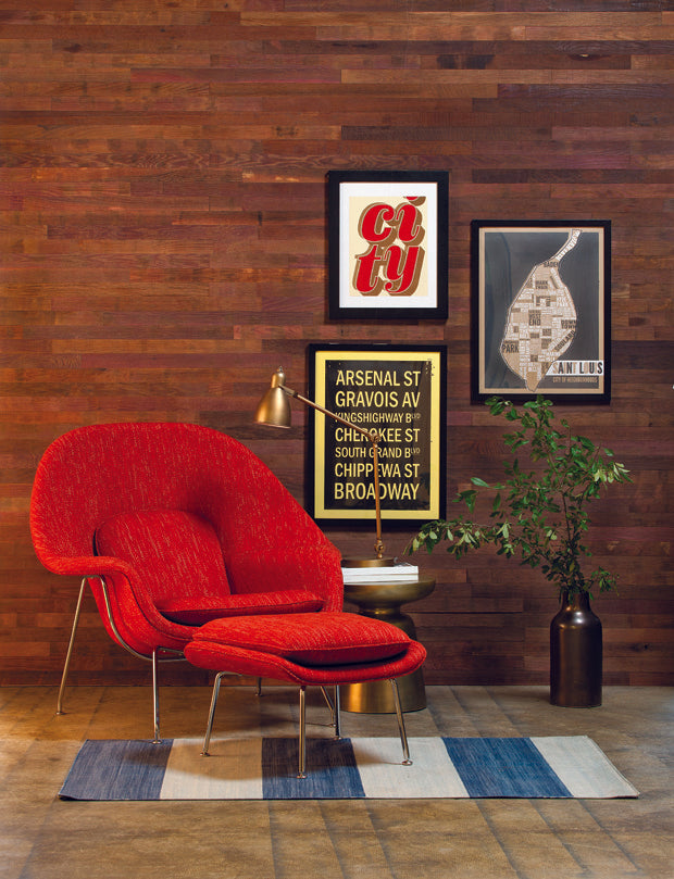 Red wine stained barnwood wall and modern red chair with metal accents add warmth to a sitting room.