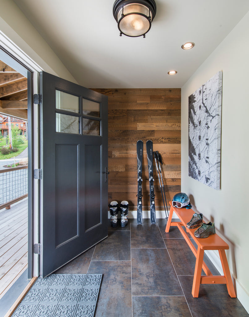Barn wood wall paneling creates a focal wall in ski cabin foyer where skis and boots