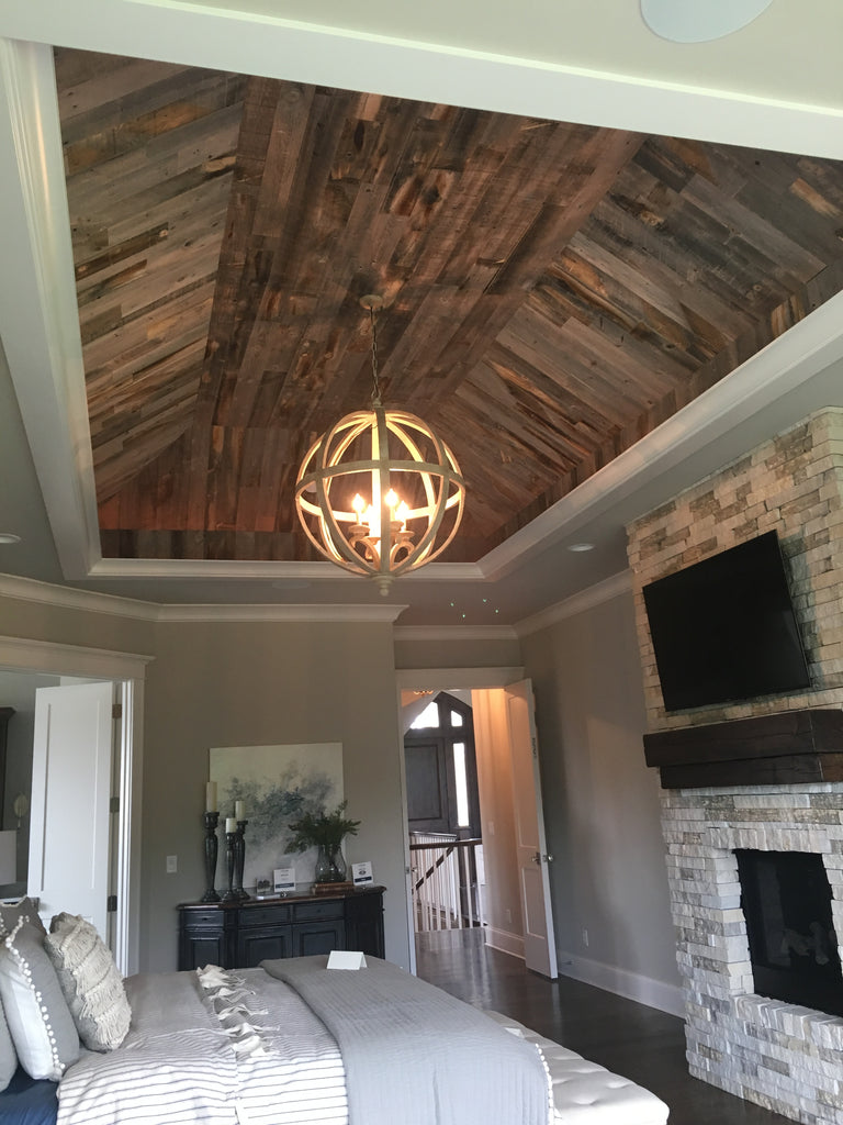 This reclaimed weathered wood vertical wood wall decor has added texture and dimension to an inverted ceiling.