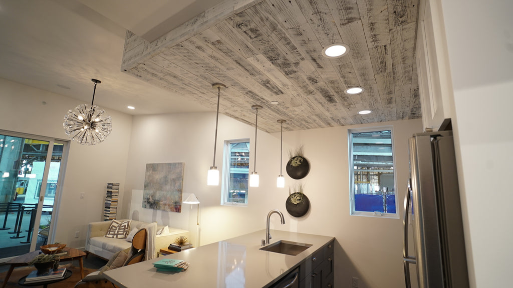 Reclaimed Weathered Wood White reclaimed wood paneling helps differentiate a kitchen space in an open floor plan by being added to the ceiling.