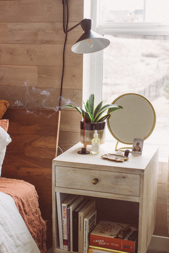 A side table in a modern boho style bedroom with a wood wall from Stikwood.