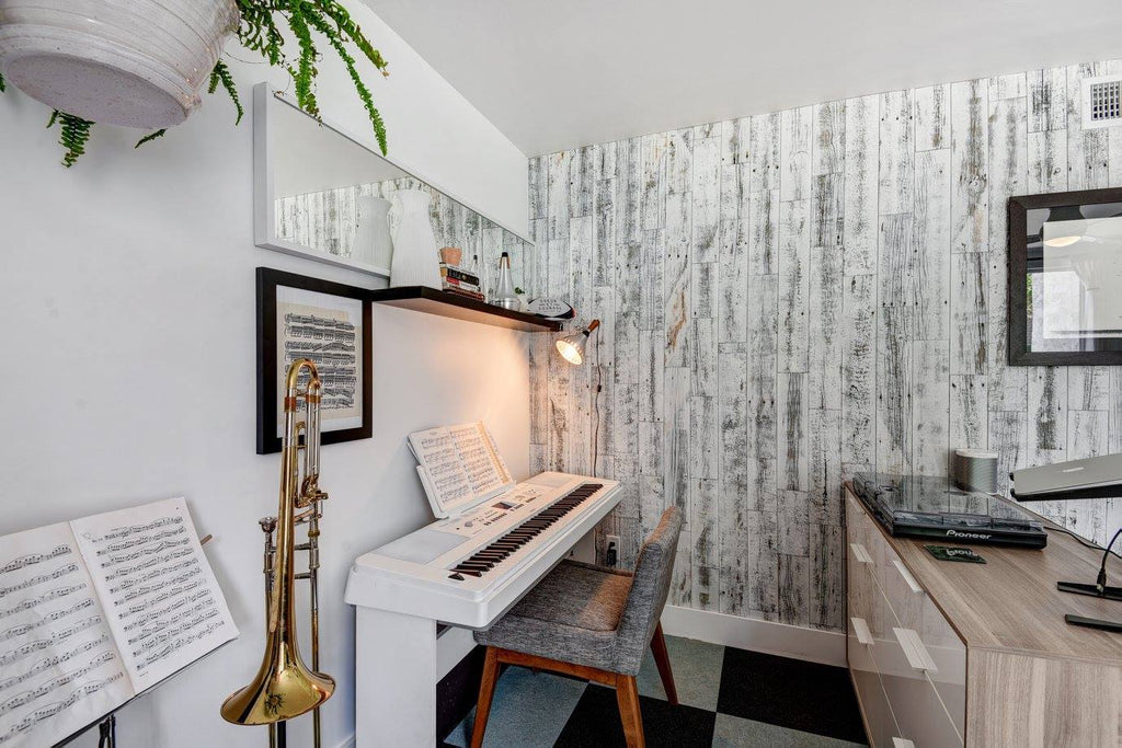 A home music room with a white stick on wood accent wall and 5-inch baseboards.