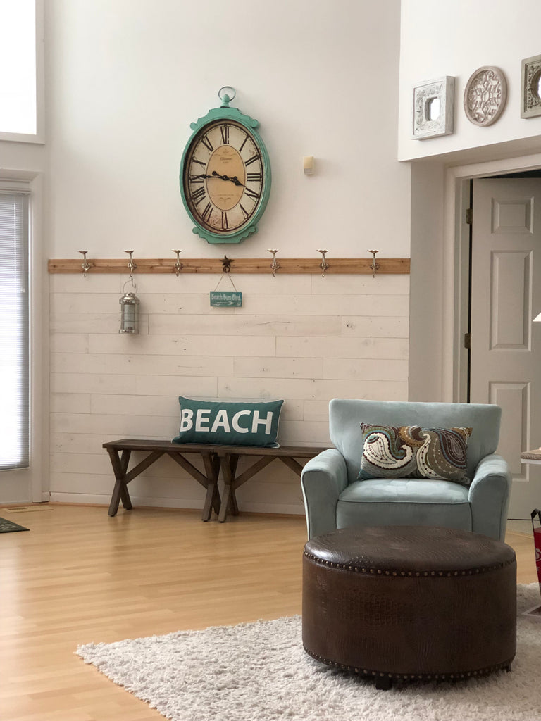 White peel and stick wood adhered to lower third of entryway creates beachy vibe