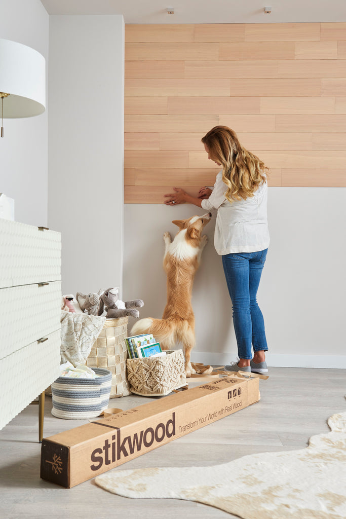 Pregnant woman installs timberwall peel and stick style paneling to a nursery wall.