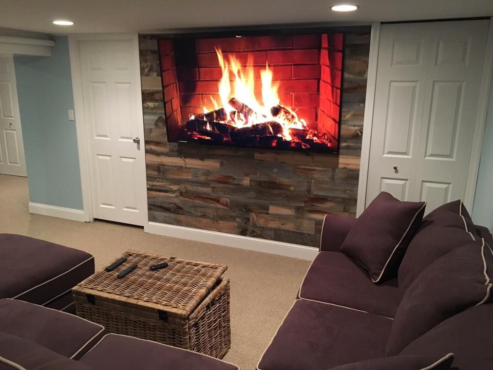 Wood plank fireplace wall with faux television fireplace hanging on it