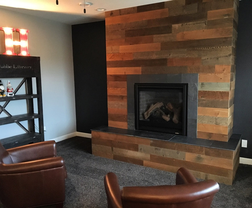 Mixed wood plank fireplace wall without a mantle surrounds wood fireplace