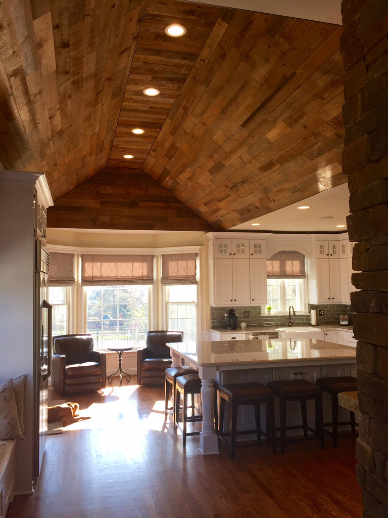 Wood planking for ceilings helps the coved ceiling mirror the wood floor in this cozy cabin kitchen.