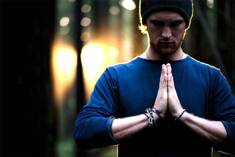 Man with hands in prayer in a shirt by eco clothing company Movement Global.