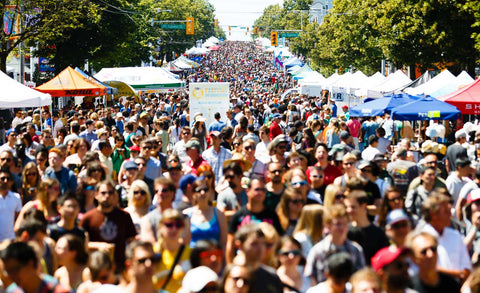 Khatsahlano Street Party is the largest free arts and music festival in Vancouver BC. A crowd of thousands walks along a closed West 4th Avenue