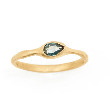 Montana Sapphire teal blue pear set horizontally on a simple textured yellow gold band