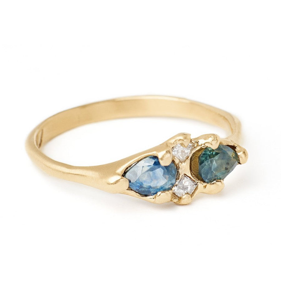 pear cut Montana blue and teal sapphire ring set with grey princess cut diamonds in our unique hand carved 14kt gold setting