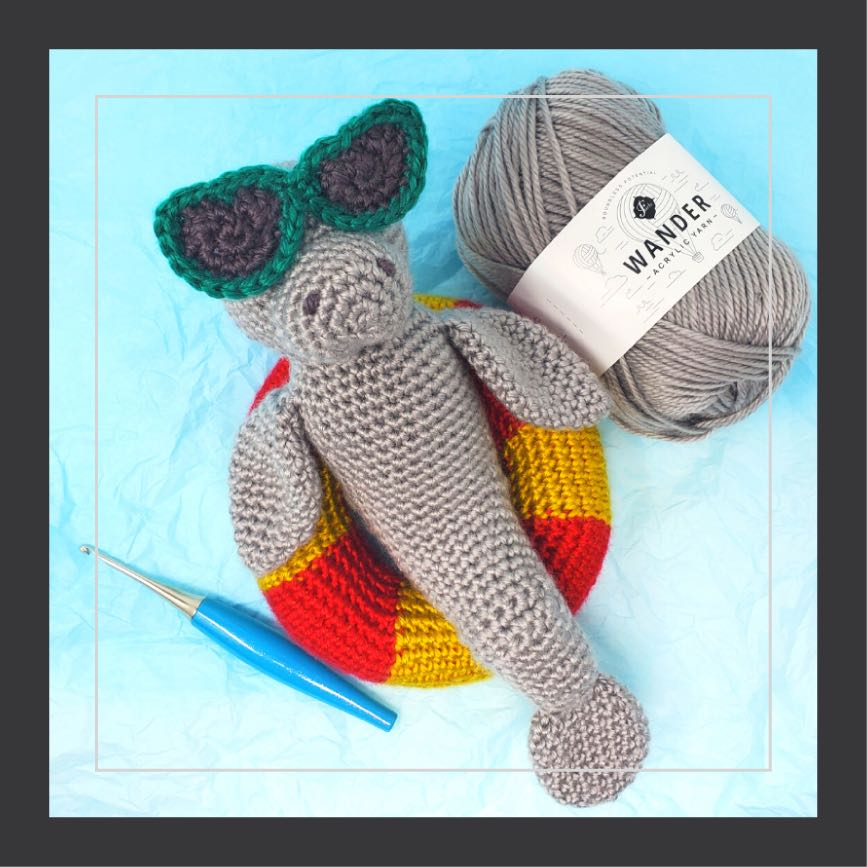 square image of amigurumi manatee with sunglasses lounging on an inflatable pool ring