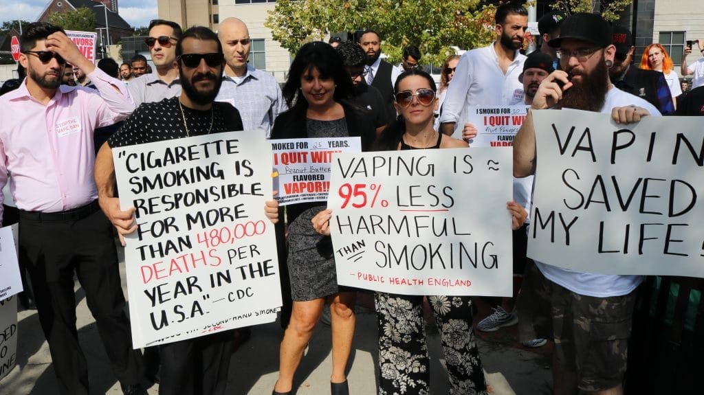 a group of people holding a sign posing for the camera