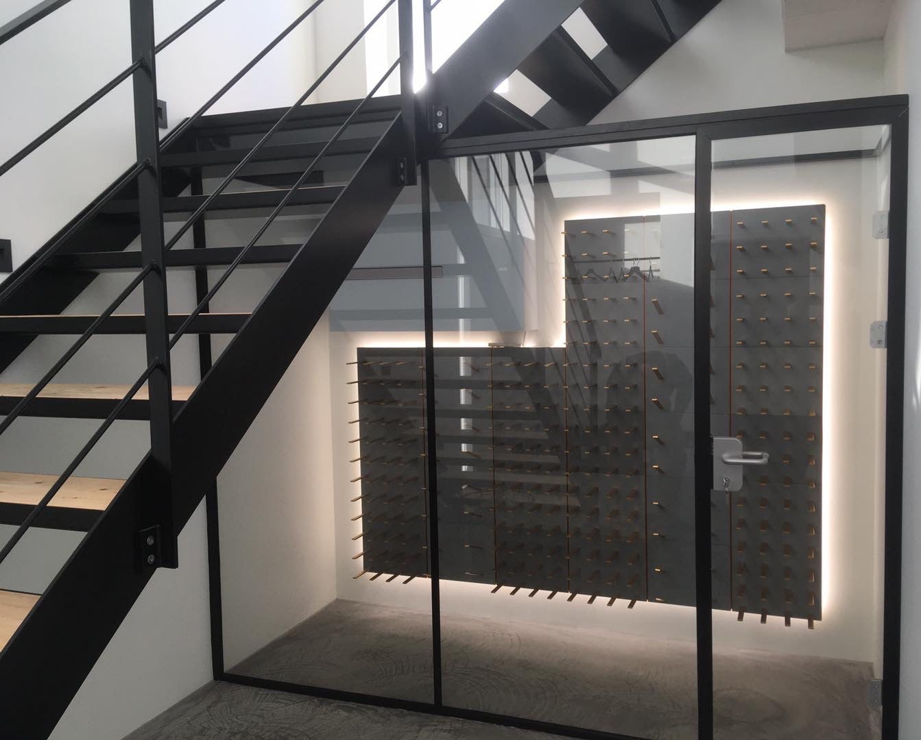 under stairs glass and metal wine room