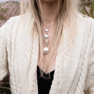A trio of Champers Necklaces worn on model, Ti in the middle.