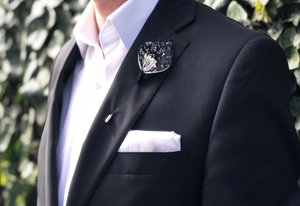Model wearing black lace and pearl center lapel pin in front of garden.