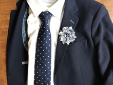 Load image into Gallery viewer, Blue and white floral lapel pin on blue jacket.