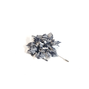 Blue and white floral lapel pin with white background.