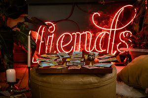 a read neon sign with the fiends logo is surrounded by foliage. In front of it is a leather-like stool with a backgammon board that tables a tarot spread. There are candles and pillows surrounding the reading.