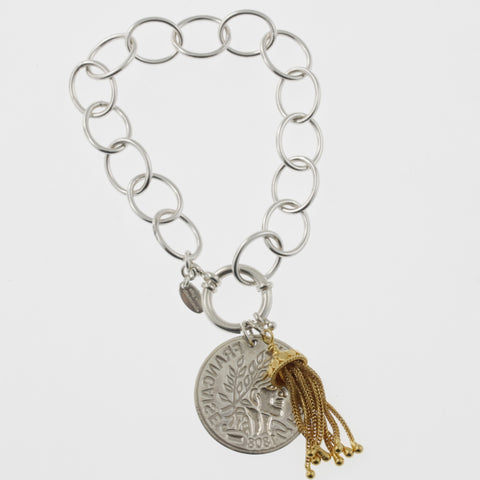 Coin bracelet on oval link chain with reproduction coin and gold plated tassle