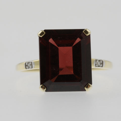 Garnet emerald cut solitaire ring with diamond shoulders in yellow gold