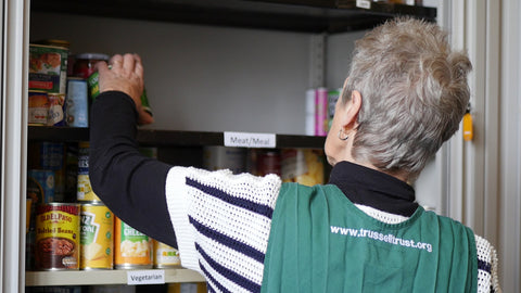 Trussell Trust volunteer stacking shelves