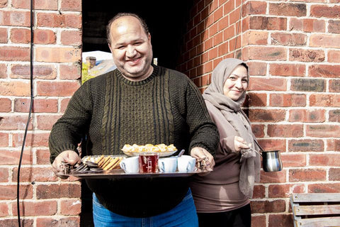Refugee Council client couple holding a tea tray smiling