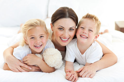 Image of a mother and her two children lay on a bed smiling together