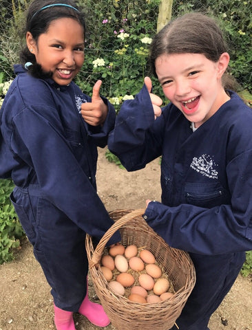 Image of two children on a Farms for City Children Farm carrying a basket of eggs