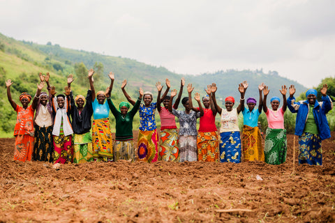 Image of group of women stood together cheering with their arms up in the air
