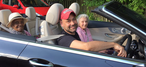 Image of a reengage volunteer in an open top car with two ladies as passengers