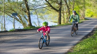 Image of a father and daughter cycling