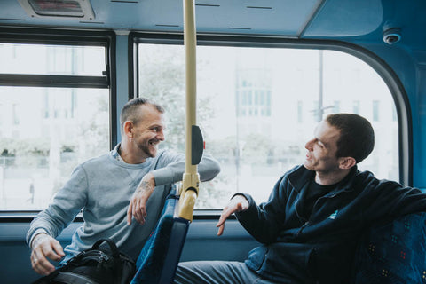Image of two men talking on a bus together