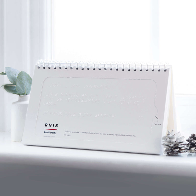 An image of the braille on the Advent of Change Braille calendar on a windowsill. It is an accessible version of the Advent of Change premium advent calendar.  The eco-friendly accessible version is fully recyclable and is a great way to give back at Christmas.