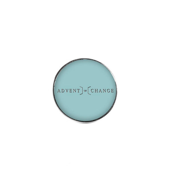 The Advent of Change metal teal pin badge to support our fundraising activities