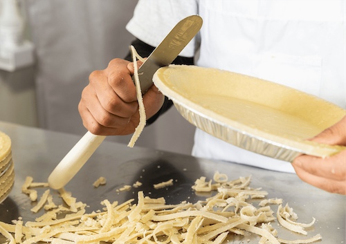 A chef cutting crust off of a pie