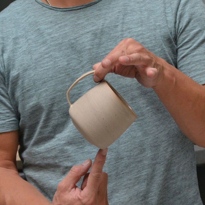 big stoneware mug with handle in hands of man