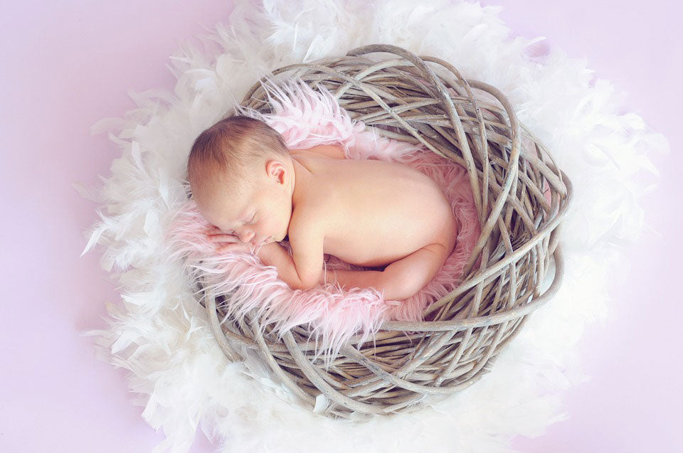 Baby curled up in a pink blanket and lattice bowl