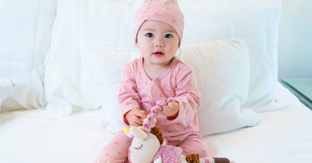 Baby in pink jumper with plush toy