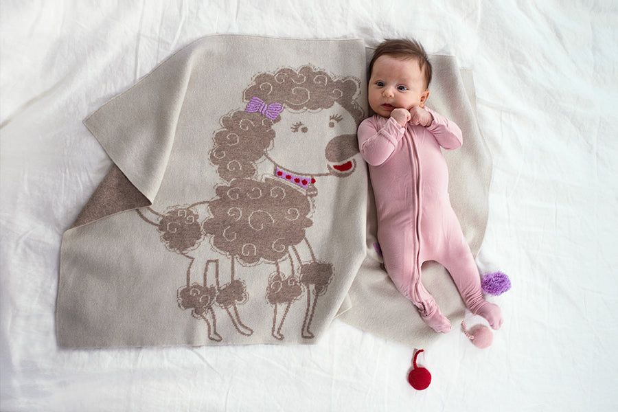 Image of baby laying on a poodle themed blanket