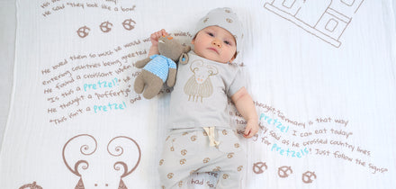 Image of baby on a blanket with a plush toy