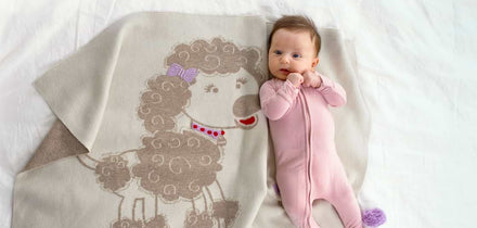 Image of a baby on a lamb themed blanket