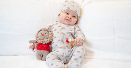 Image of smiling baby holding plush toy