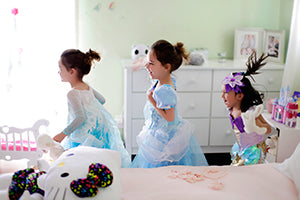Three young girls in princess dresses playing in a bedroom.