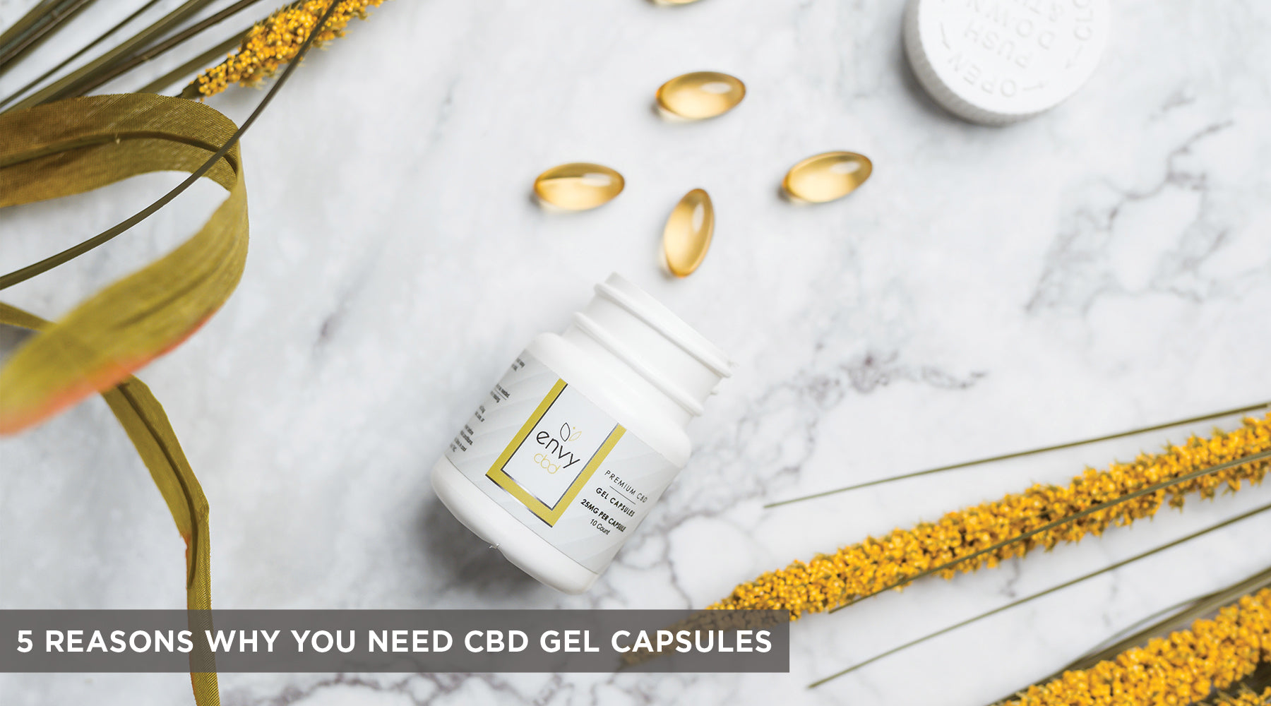 CBD Gel Capsules container is uncapped and laying label side-up on a white tabletop surface with several gel capsules displayed.